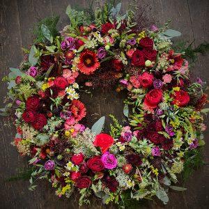 Fyldig og farverig rundpyntet blomsterkrans til begravelse i Horsens og omegn