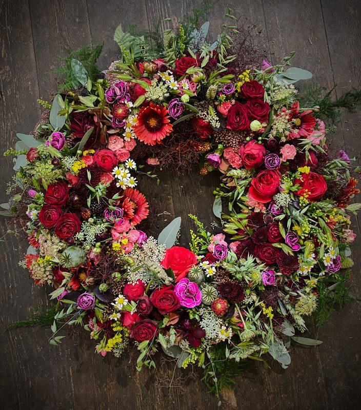 Farverig blomsterkrans til begravelse