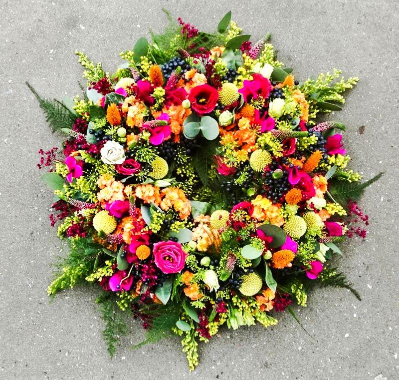 Kulørt rundpyntet krans – professionelt sorgbinderi til begravelse bisaettelse Horsens